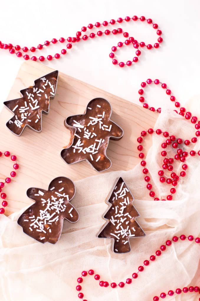 Cookie Cutter Christmas Fudge en una tabla de cortar con cuentas rojas.