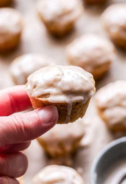 Mano sosteniendo uno de los Mini Chai Muffins con Vanilla Bean Glaze