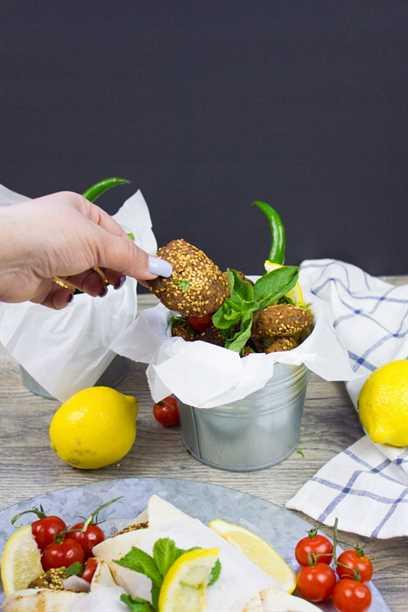 Un balde de falafel rodeado de un limón y ramitas de menta