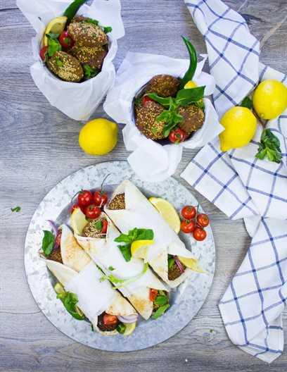 Un plato de falafel se envuelve junto a cubos de falafel recién frito rodeado de menta, tomates y limones