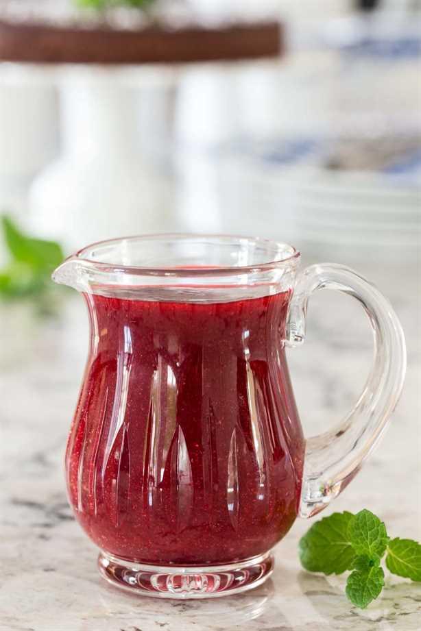 Foto de una jarra de vidrio llena de Easy Raspberry Coulis sobre una encimera de cocina de granito.