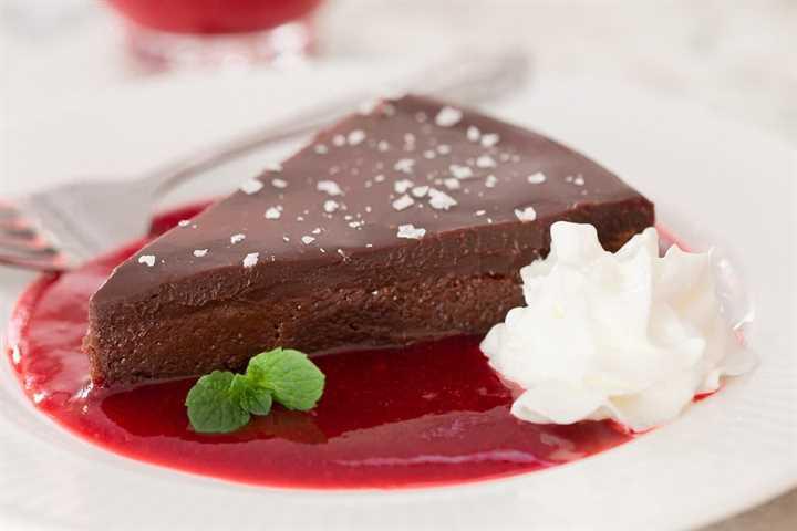 Foto de una rebanada de postre de chocolate en un plato de postre en una piscina de Ridiculous Easy Raspberry Coulis.