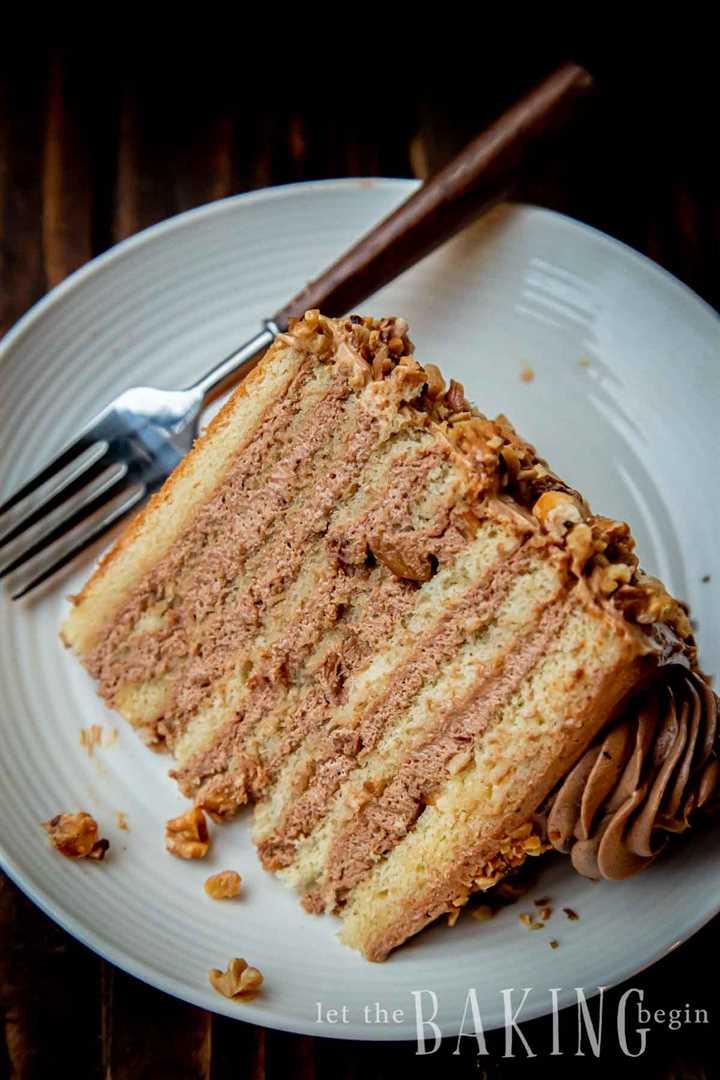 Rebanada de pastel empapado de ron en capas en un plato blanco con tenedor.