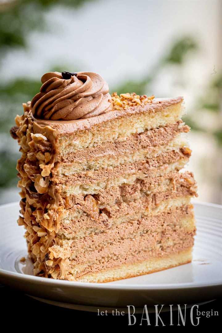 Una rebanada de pastel en capas con glaseado de café sentado en un plato blanco.