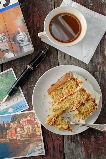 Rebanada parcial de pastel de crema italiana con una taza de café y un libro de viajes.