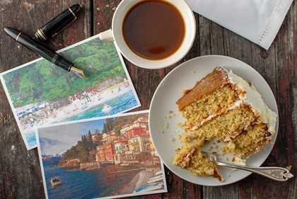 rebanada de pastel de crema italiana con postales y una pluma estilográfica