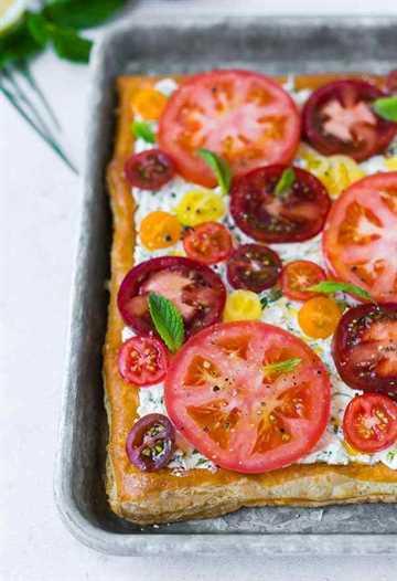 Esta fresca tarta de tomate con ricota con hierbas sabe a verano en una costra de hojaldre escamosa. Es fácil de hacer y visualmente impresionante. ¡Hazlo para tu próxima fiesta!