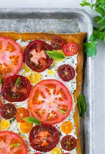 Imagen de ricotta de hierbas y tarta de tomate fresco, tomada desde arriba. Decorado con hojas de menta.