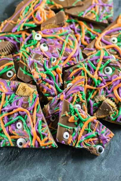 Corteza de Halloween púrpura, verde y naranja con globos oculares y tazas de mantequilla de maní en un tablero de pizarra.