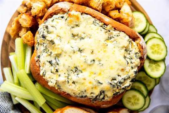 tabla de madera con bol de pan relleno de salsa de alcachofas y espinacas, rodeado de verduras y pan