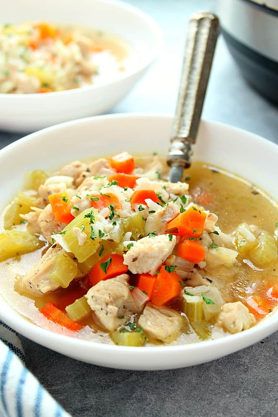 Sopa de pollo y arroz en un tazón blanco al lado de la olla instantánea. Receta instantánea de sopa de pollo y arroz