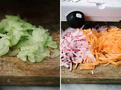 Cómo hacer envolturas de lechuga Whole30 cherry chicken salad. Apio en rodajas finas sobre una tabla para cortar. Julienned rábanos y zanahorias en una tabla de cortar.