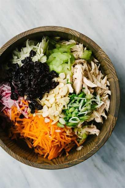 Uma tigela de madeira cheia dos ingredientes para o recheio completo da salada de frango 30: frango assado, cenoura, pepino, erva-doce, aipo, cebola verde, cerejas secas e amêndoas picadas.