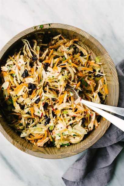 Uma saladeira de madeira cheia de 30 salada de frango inteiro misturada com vinagrete balsâmico, pronta para ser recheada com folhas de alface para um envoltório de salada de frango paleo.