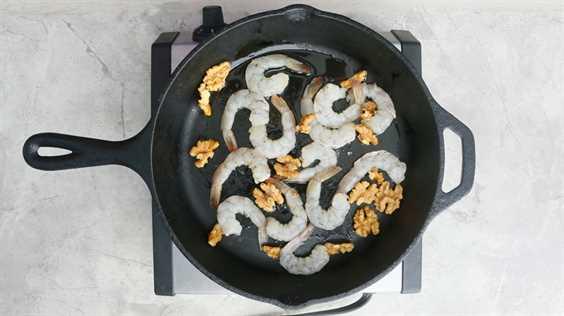 saltear camarones y nueces en una sartén caliente
