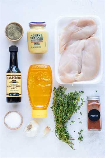 Miel, mostaza, tomillo, pimentón, sal y ajo como ingredientes para una receta.