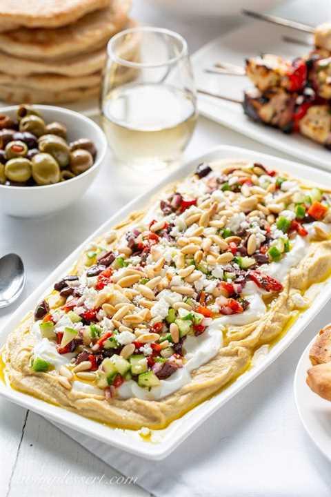 Una fuente de salsa de hummus griego en capas con yogur, aceitunas, pimientos rojos, piñones y pepinos