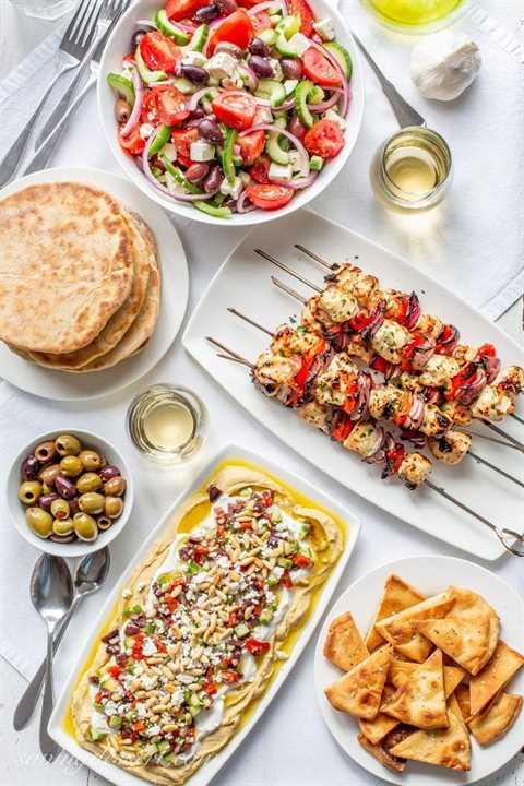 Una cena griega con brochetas de pollo griego a la parrilla, un plato de ensalada griega, salsa de humus griego en capas, pan de pita integral, vino y aceitunas