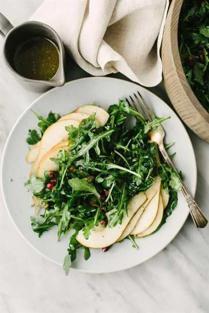 Ensalada de pera rúcula con granadas y pistachos en un plato azul con un tenedor de plata, una pequeña jarra de vinagreta de mostaza y champán.