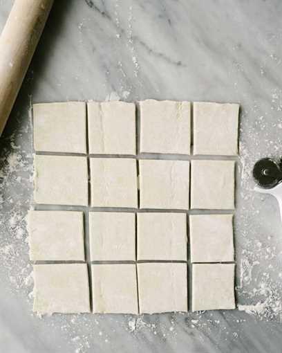 Hojaldre descongelado cortado en 16 cuadrados para hacer tartaletas de calabaza.