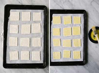 Cuadrados de hojaldre en una bandeja para hornear, marcados y atracados, listos para ser rellenados con calabaza moscada, cebolla caramelizada y queso ricotta.