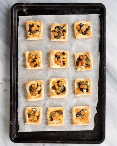 Mini tartas hinchadas y doradas en una bandeja para hornear cubierta con calabaza, cebolla caramelizada y queso ricotta.