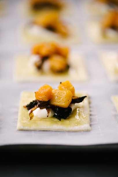 Un solo hojaldre cuadrado en una bandeja para hornear cubierto con calabaza, cebolla caramelizada y queso ricotta.