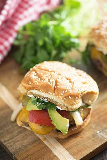 ¡Cubrí estas hamburguesas de fajita de carne con queso cheddar, aguacate, cilantro y crema agria! ¡No te olvides de los pimientos y cebollas asados!