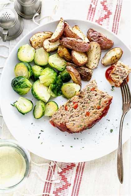 un plato con una rebanada de pastel de carne de pavo con papas y coles de Bruselas