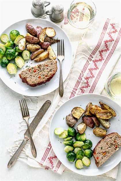 Una vista desde arriba de una mesa con dos platos de pastel de carne, coles de Bruselas, papas asadas y un lino estampado blanco y rojo