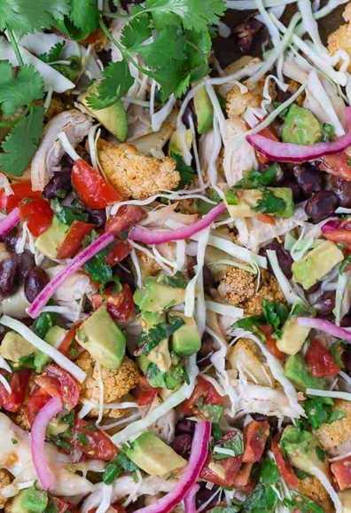 Imagen de coliflor asada cubierta con una variedad de sabores del sudoeste: cebollas rojas en escabeche, tomates, repollo, aguacate, frijoles negros y queso rallado.