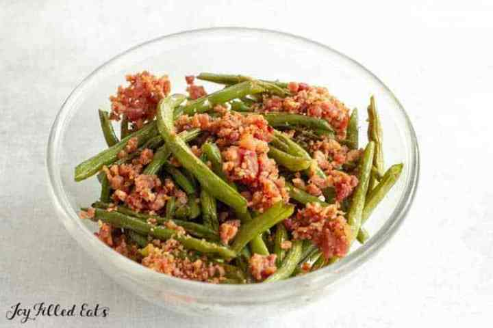 Baked green beans in a glass bowl with bacon