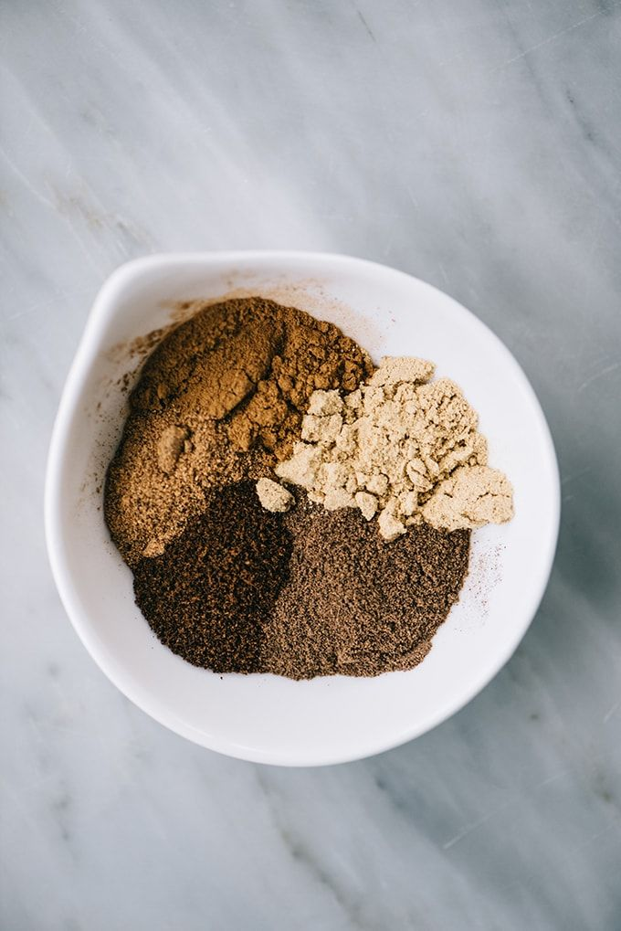 Mix gingerbread spices in a small white bowl to mix with gingerbread spice nuts.