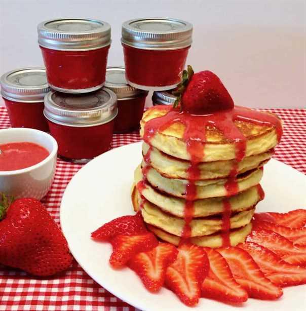 pila de panqueques con salsa de fresa y fresa en la parte superior