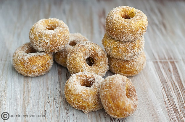 Pumpkin donuts stacked on a table.