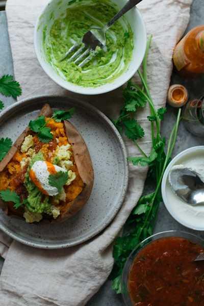 Un desayuno cargado de batata en un plato junto a tazones de coberturas
