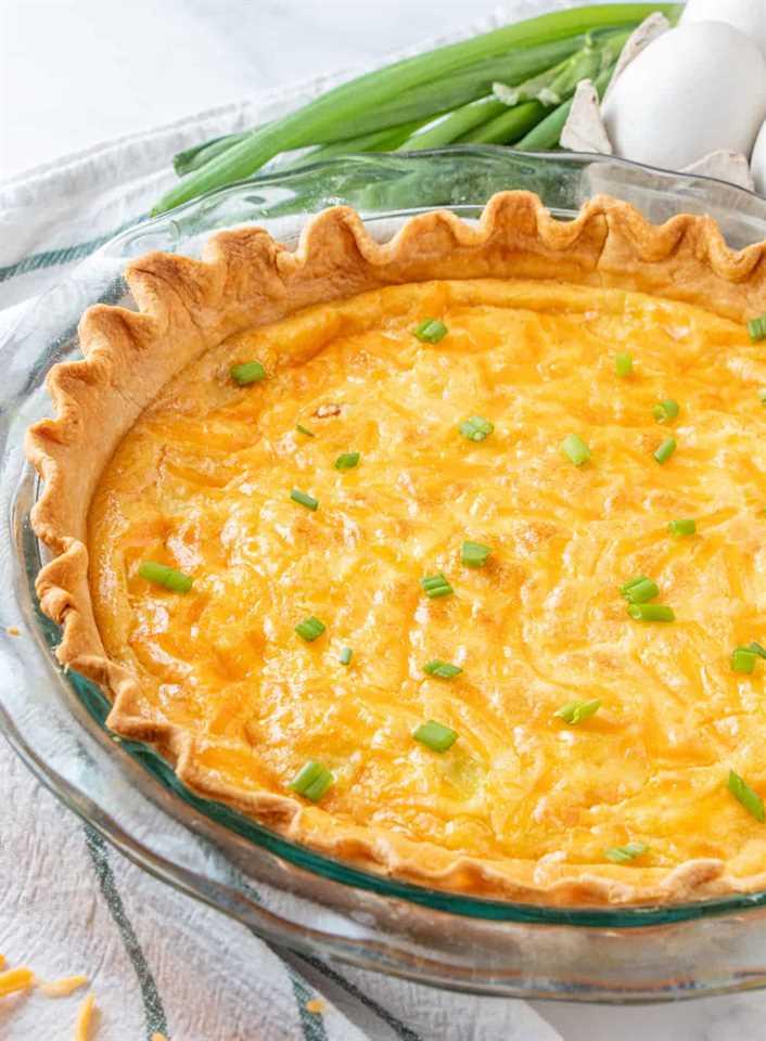 Quiche de jamón y queso al horno en un plato de tarta antes de cortar con cebollas verdes