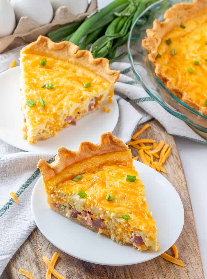 Quiche en dos platos cubiertos con cebollas verdes y adornado con queso