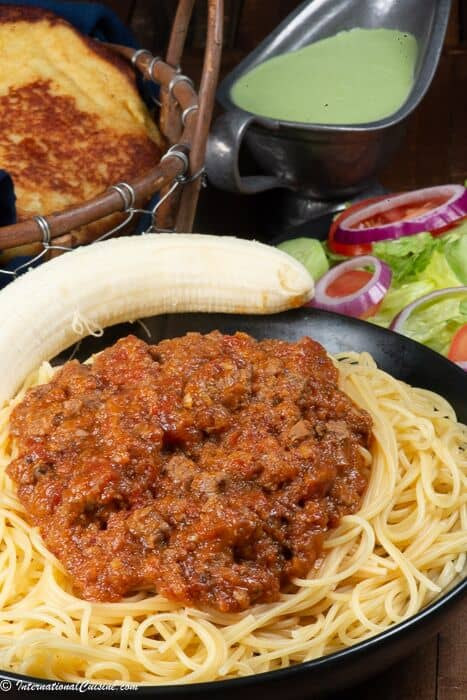 A plate full of pasta with Somali pasta sauce called suugo along with a banana.