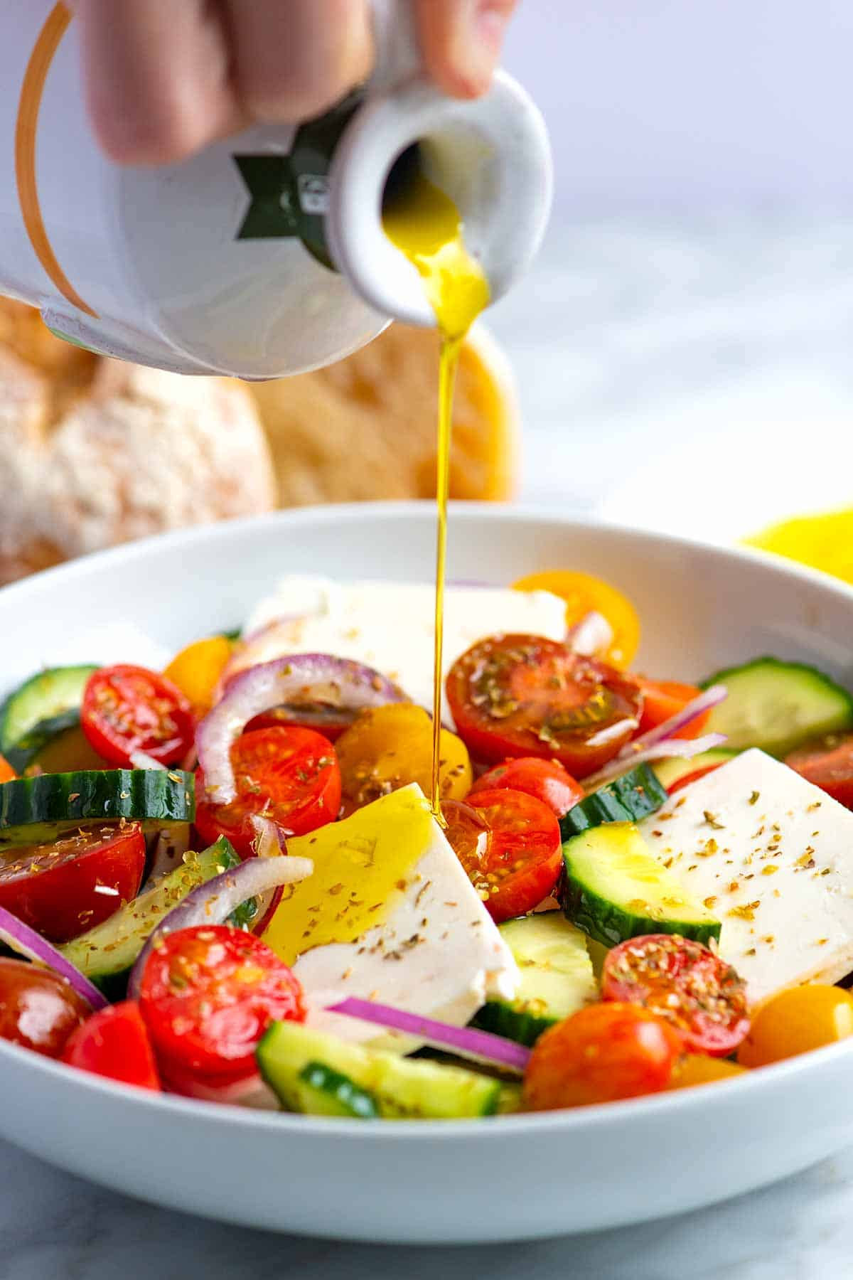 The olive oil is poured onto a Greek salad.