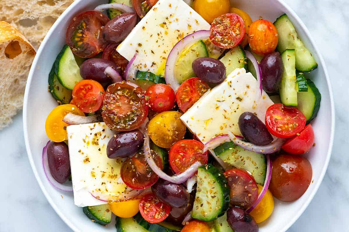 A bowl filled with a salad made of cucumbers, tomatoes, olives, red onion, and feta cheese.