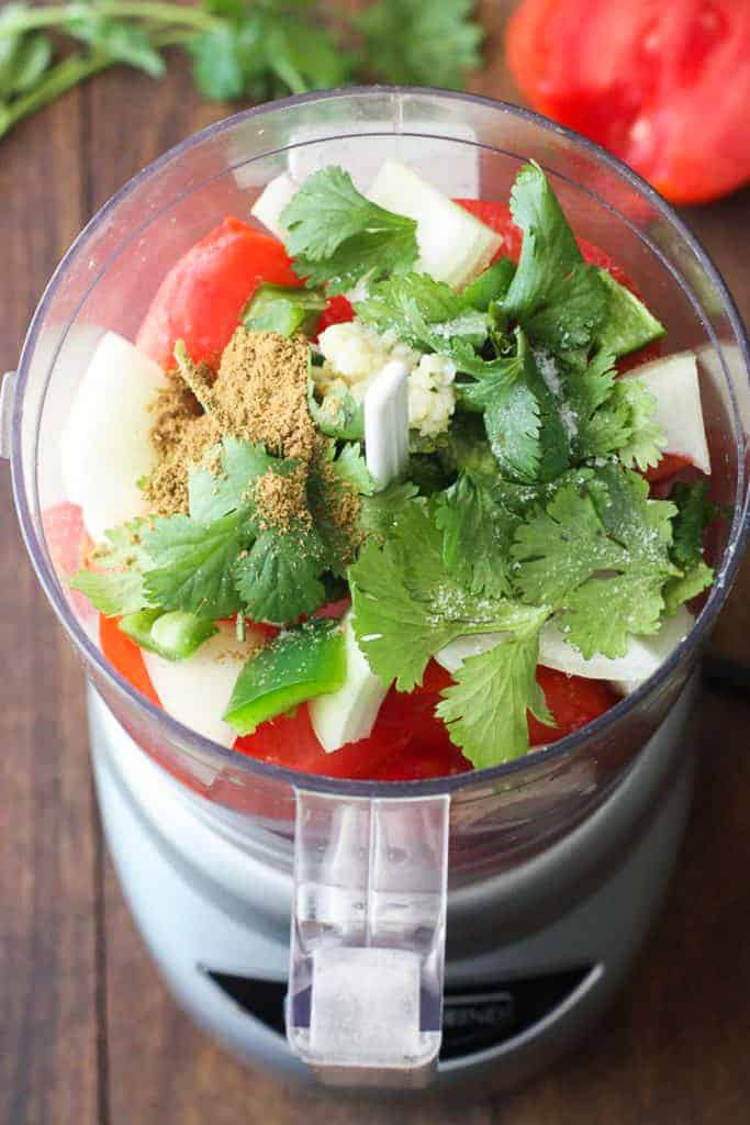 A food processor with the ingredients to make the sauce, including tomatoes, coriander, onion, garlic, and cumin.
