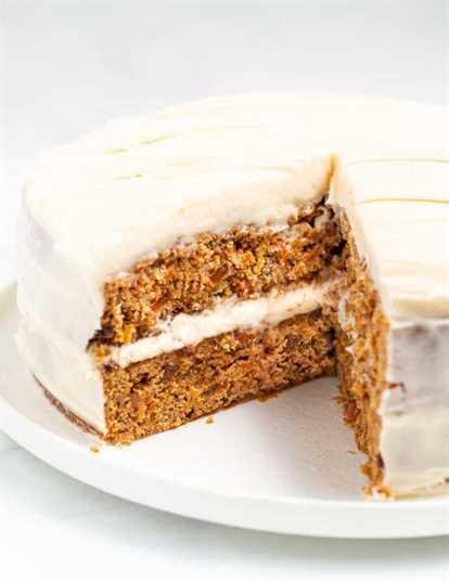 Un pastel de zanahoria vegano en un plato con una rodaja cortada, mostrando adentro