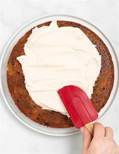 glaseado de queso crema vegano se extiende sobre una capa de pastel con una espátula
