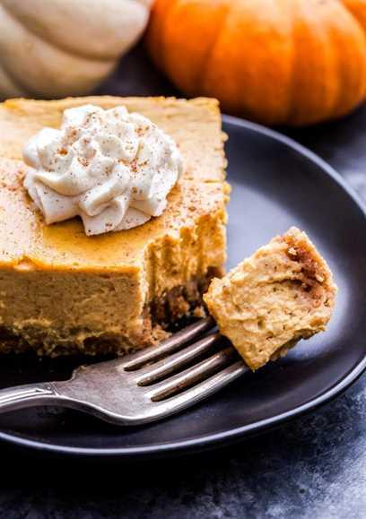 Pieza cuadrada de Creamy Pumpkin Pie Bar cubierta con crema batida y una pieza cortada con un tenedor.