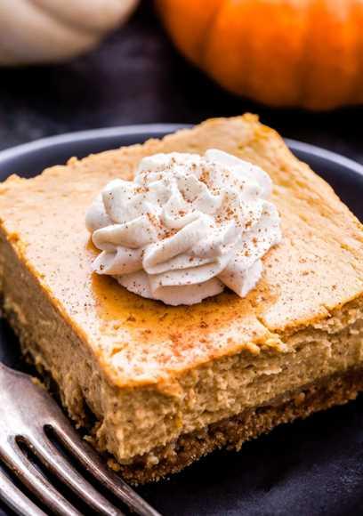 Foto del primer de Creamy Pumpkin Pie Bar cubierto con crema batida en un plato negro.