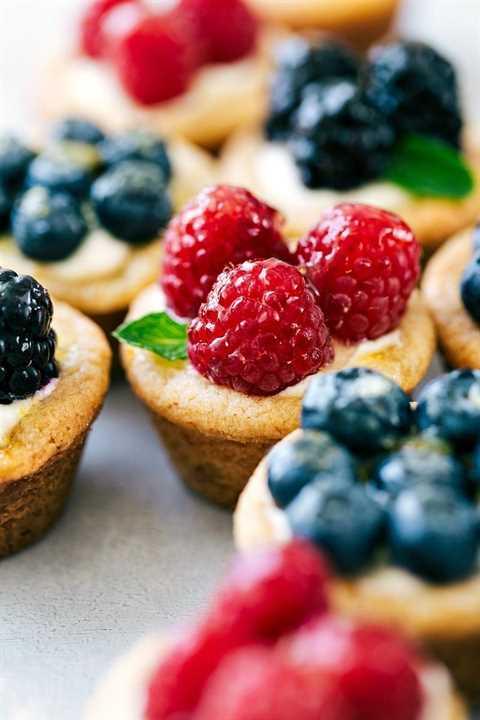 Imagen cercana de las mini tartas de frutas con frambuesas, arándanos, moras y menta fresca