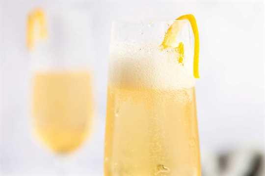 dos flautas de champán con cóctel de flor de saúco y guarnición de cáscara de limón