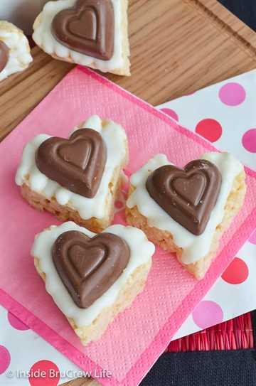 Corazones Krispie de Reese de chocolate blanco: un corazón de taza de mantequilla de maní y chocolate blanco hacen que estos krispie de arroz sean un refrigerio divertido para el día de San Valentín. #ricekrispietreats #nobake #peanutbuttercups #reathapedtreats #valentinesday #reeses
