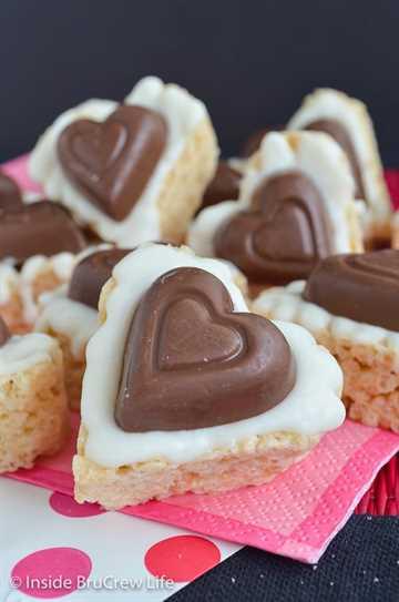 Corazones Krispie de Reese de chocolate blanco: un corazón de taza de mantequilla de maní y chocolate blanco hacen de estos los mejores dulces de arroz krispie. Haga esta receta fácil sin hornear para el día de San Valentín este año. #ricekrispietreats #nobake #peanutbuttercups #reathapedtreats #valentinesday #reeses